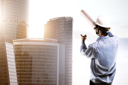 office building: young builder standing and pointing at skyscraper Stock Photo