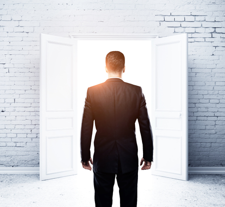 white men: young man in brick room with open doors Stock Photo