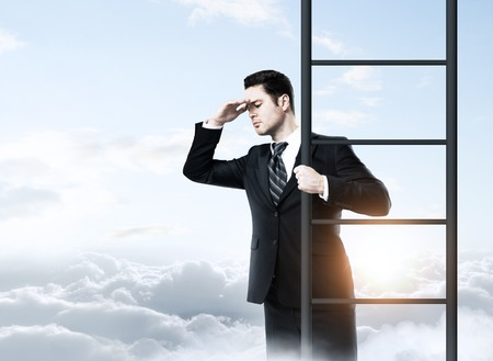climbing ladder: businessman standing on ladder and looking to sky