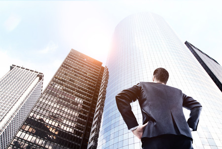 men in suit: businessman in suit looking on big skyscraper