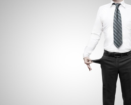 turned out: businessman standing with pockets turned inside out on gray background