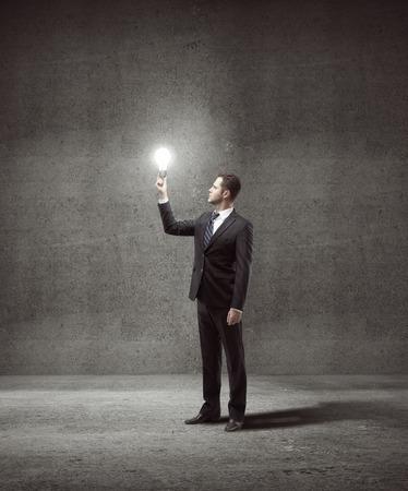 lightbulb: businessman holding lightbulb in gray concrete room