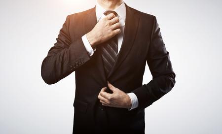 traje: empresario ajusta la corbata en el fondo blanco Foto de archivo