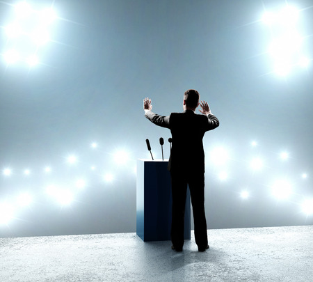 hablar en publico: empresario de pie en el podio y se cierra sobre los brotes