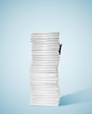 apilar: Hombre de negocios joven que sube para arriba una enorme pila grande de papel Foto de archivo