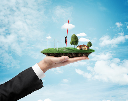 beautiful heaven: hand holding landscape with eco wind turbine and climbing businessman Stock Photo