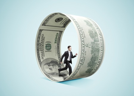 prosperidad: hombre de negocios que se ejecuta en rueda de dinero en el fondo azul Foto de archivo
