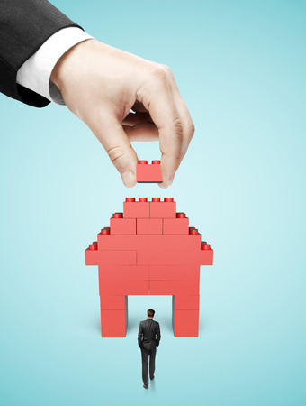 build structure: hand build house blocks on blue background Stock Photo