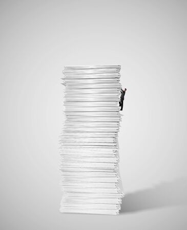 stack of paper: young businessman climbing up a huge big stack of paper