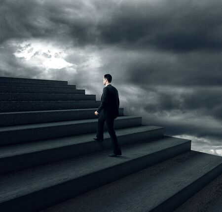 ascend: businessman climbing on stairs in bad weather