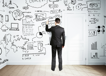 drawing a plan: businessman drawing plan business concept on wall