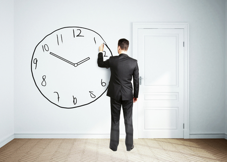 office wall: businessman drawing clock on wall Stock Photo