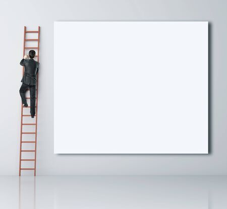 ladder: man climbing on ladder and blank poster Stock Photo