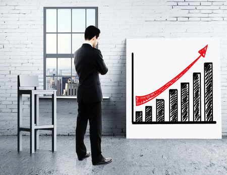 growth: businessman looking at growth chart on desk