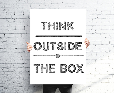 think outside the box: businessman holding poster with think outside the box