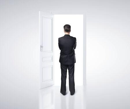 open door: businessman in white room with doors open