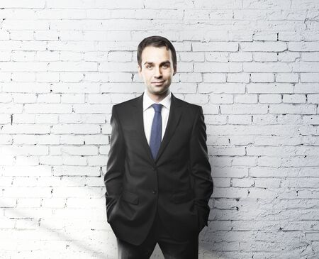 standing against: businessman standing against a brick wall Stock Photo