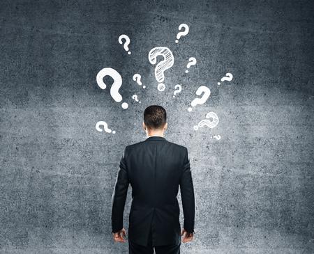 pensando: hombre de negocios pensando y mirando en el muro de hormig�n