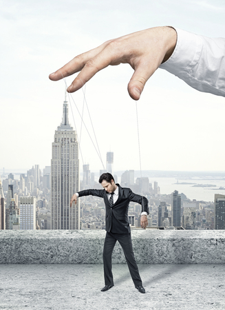 tiedup: Businessman marionette on ropes controlled  hand Stock Photo