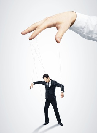 exploitation: Businessman marionette on ropes controlled  hand Stock Photo