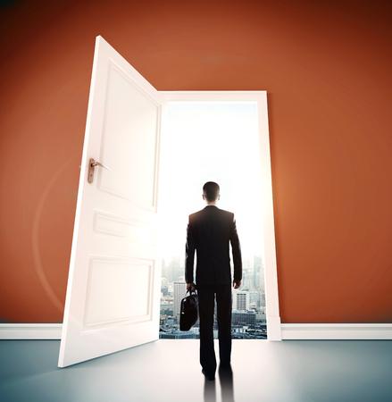 room door: businessman with briefcase open door to city