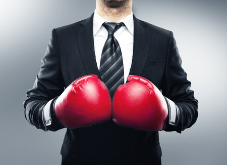 boxing equipment: businessman in boxing gloves isolated on gray