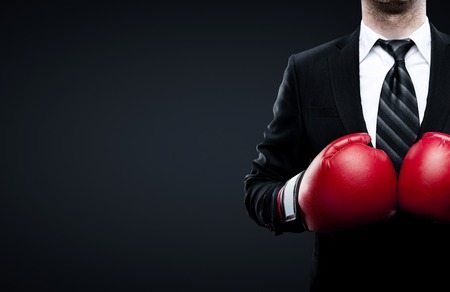 protective suit: businessman in boxing gloves isolated on black background