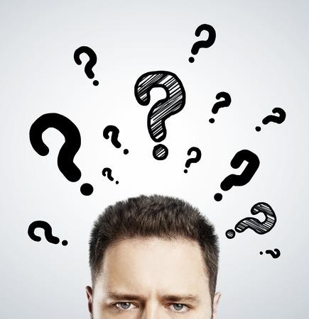 man met vragen symbool boven het hoofd op een grijze achtergrond