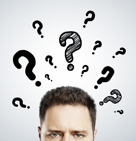 question concept: man with questions symbol over head on gray background