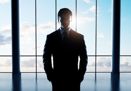 standing businessman: young businessman standing in airport