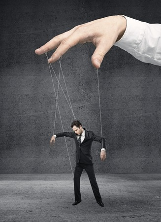 Businessman marionette on ropes controlled  hand Banco de Imagens