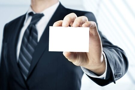 man handing a blank business card over blue background