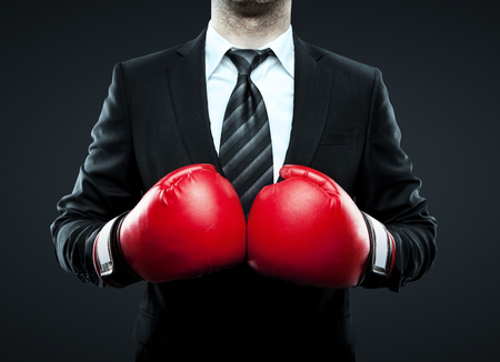 boxing knockout: businessman in boxing gloves isolated on gray