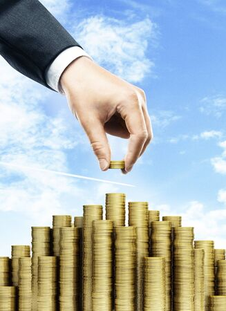 business money: businessman puts a coin in the stack