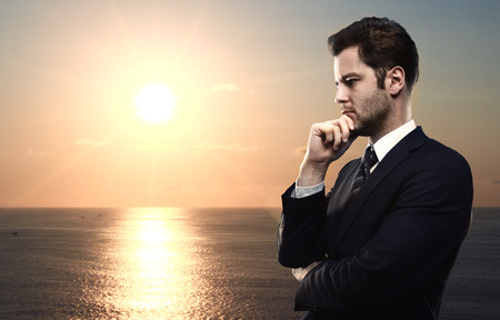 clop: businessman thinking on a sunset in ocean background