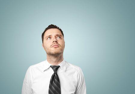 businessman thinking: young businessman thinking on blue background