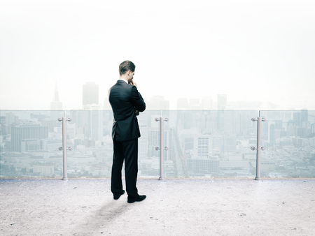 standing businessman: businessman thinking standing on roof and looking on city