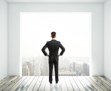 big window: businessman looking in big window in room