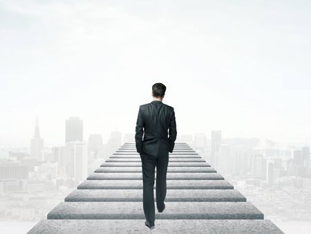difficult journey: businessman walking in the sky and city Stock Photo