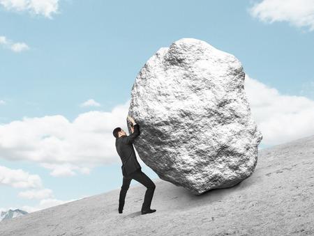 segurar: empresário empurrando pedra-se no monte