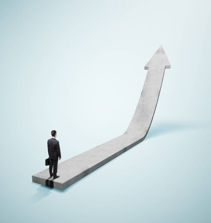 businessman in suit standing on gray arrow Stockfoto