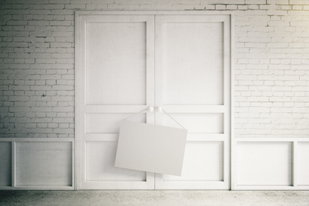 white door: blank poster hanging on the handle of a closed door Stock Photo