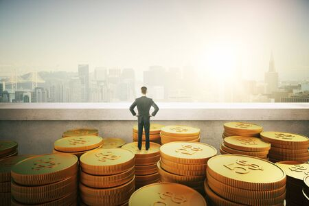 investment concept: businessman standing on gold coins and looking on city Stock Photo