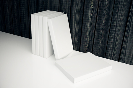 books on a wooden surface: Stack of blank white books leaning on dark wooden wall. Mock up, 3D Render Stock Photo