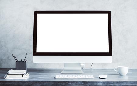 コーヒー カップと他の項目と木製のデスクトップの空白いコンピューター画面。モックアップします。 写真素材