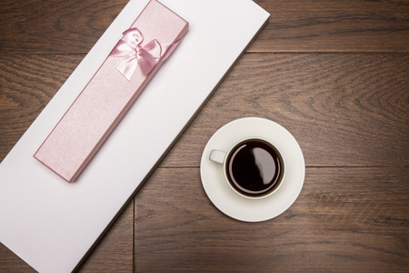 girly: Topview of wooden desktop with girly gift case and coffee cup