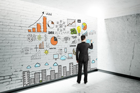 schemes: Research concept with businessman drawing colorful business schemes on white brick wall. 3D Render Stock Photo