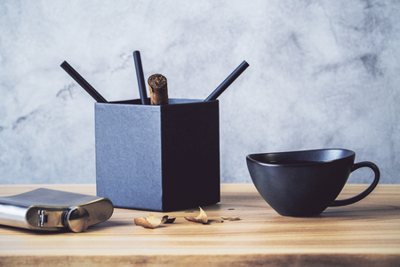 pencil holder: Desktop with black pencil holder, coffee cup and flask on concrete wall background