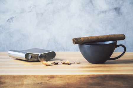 filing: Desktop with cigar on top of coffee cup, silver flask and filing on concrete background Stock Photo