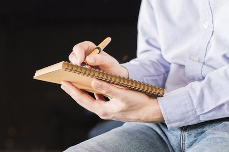 hombre escribiendo: Lateral de sexo masculino con camisa de color púrpura y pantalones vaqueros por escrito en el bloc de notas sobre fondo negro